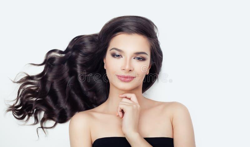 Nette Frau mit dem Schlag des gelockten Haares auf Weiß Schönes weibliches vorbildliches Face lizenzfreies stockfoto