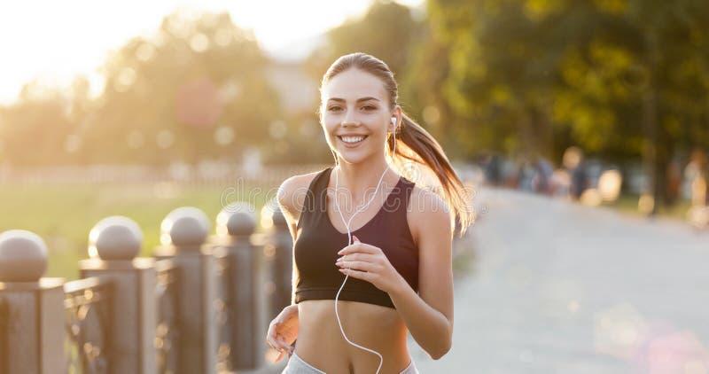 Nette Frau mit den Kopfhörern, die in Park laufen lizenzfreie stockfotografie