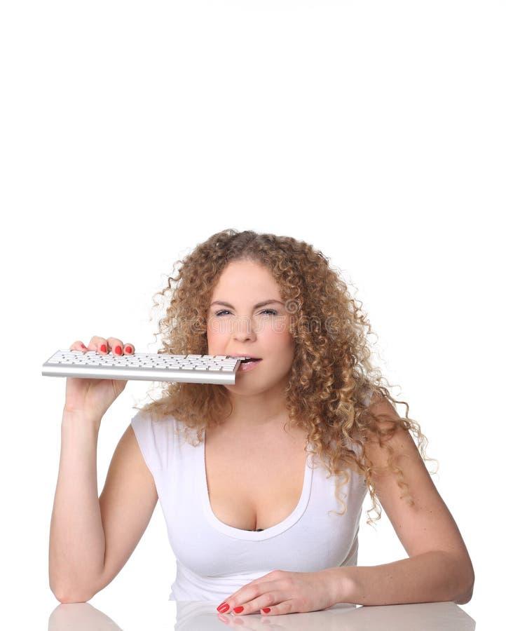 Nette Frau, rotes gelocktes Haar, sitzend mit Tastatur in den Zähnen stockfotos