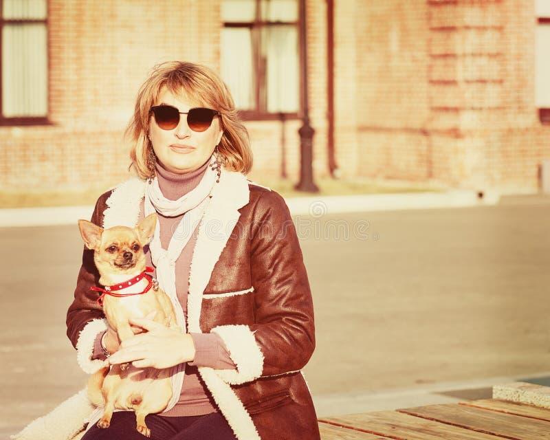 Nette Frau und ihr Chihuahua-Hund auf Natur-Hintergrund lizenzfreies stockfoto