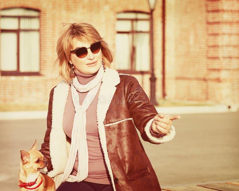 Nette Frau und ihr Chihuahua-Hund auf Natur-Hintergrund stockfotografie