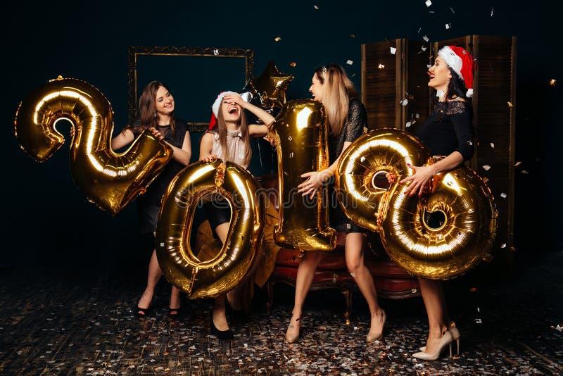 Nette Frauen in den Weihnachtshüten an der Partei des neuen Jahres stockfotos