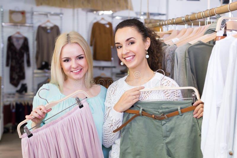 Nette Frauen, die Rock und Hose kaufen lizenzfreie stockfotos