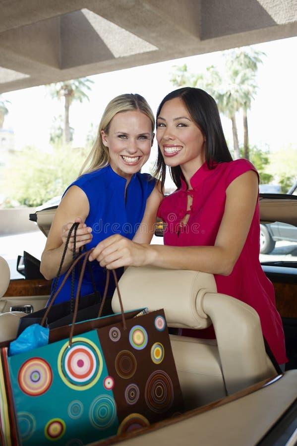 Nette Frauen mit Einkaufstaschen im Kabriolett lizenzfreies stockfoto