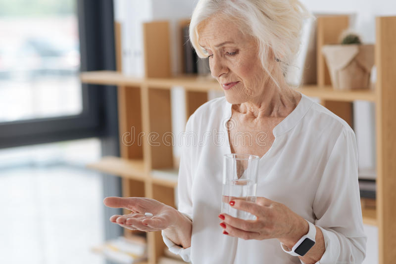 Nette freudlose Frau, die eine Palme mit der Pille hält stockfotos