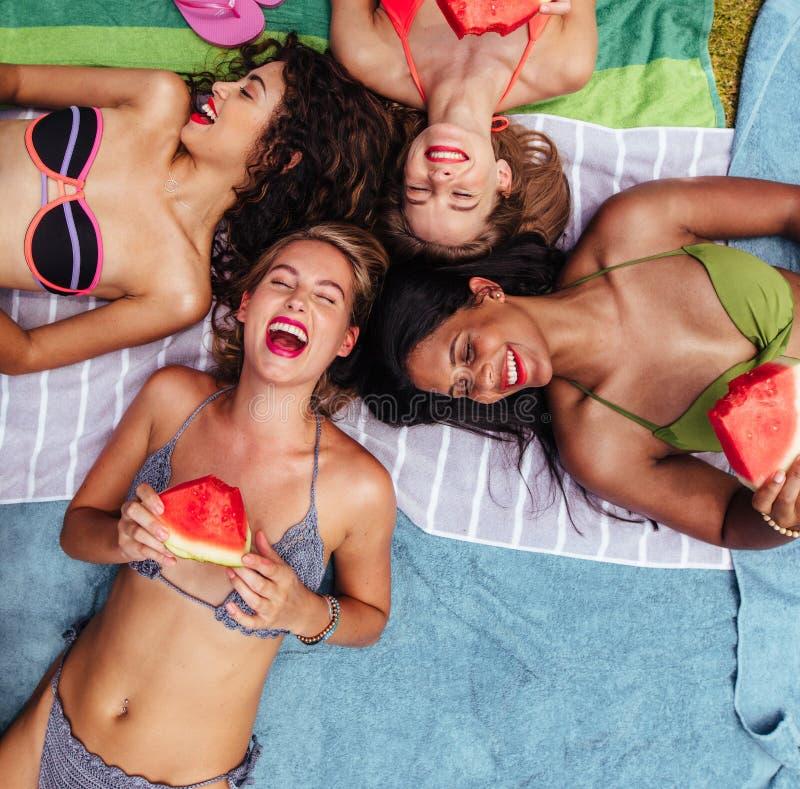 Nette Freunde, die durch Poolside mit Wassermelone liegen lizenzfreies stockfoto
