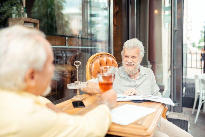 Nette gealterte grau-haarige Männer, die ihren Ruhestand feiern stockbild