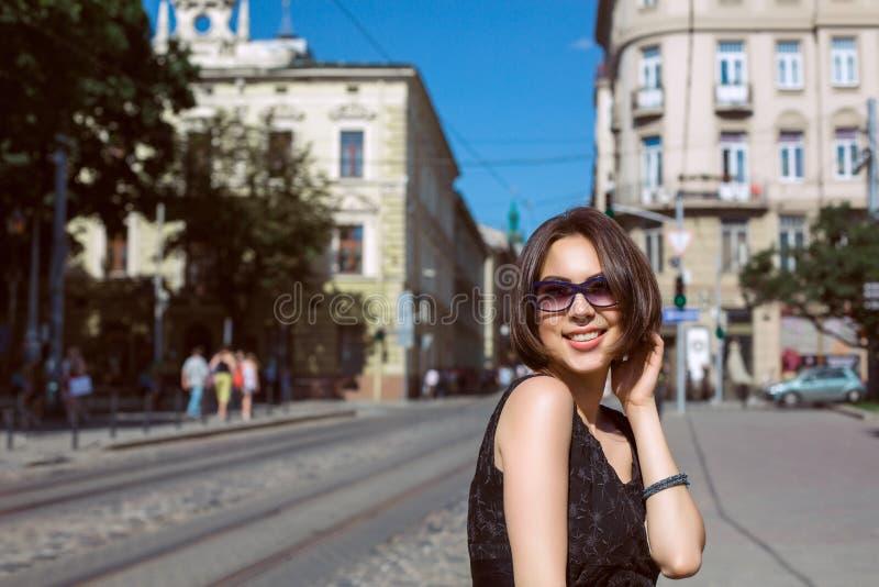 Nette gebräunte tragende Gläser der Brunettefrau und stilvolles Kleid lizenzfreies stockfoto