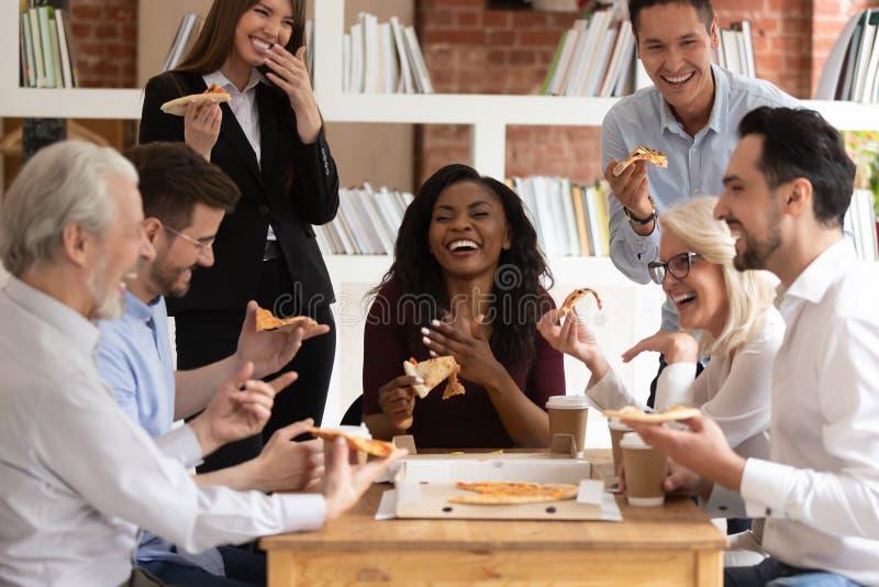 Nette gemischtrassige Bürogeschäftsleute lachen, Mitnehmerpizza zusammen zu teilen lizenzfreies stockfoto