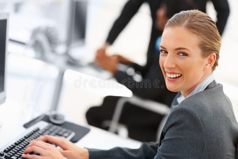 Nette Geschäftsfrau, die an dem Computer arbeitet lizenzfreie stockfotografie