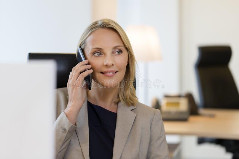 Nette Geschäftsfrau am Handy im Büro stockbild