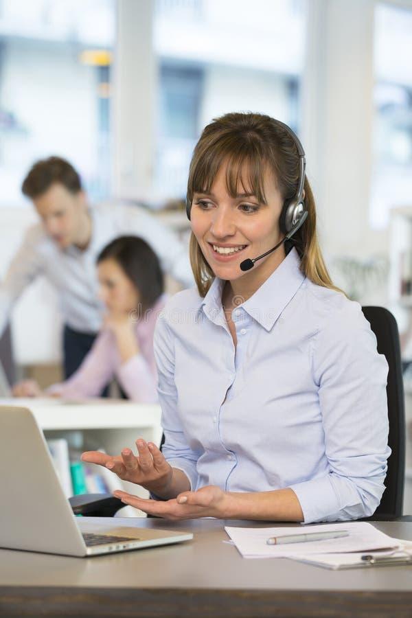 Nette Geschäftsfrau im Büro am Telefon, lizenzfreie stockfotografie