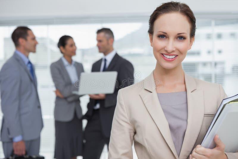Nette Geschäftsfrauholdingdateien, die an der Kamera lächeln lizenzfreies stockbild