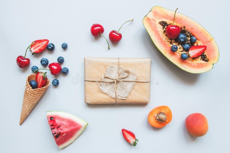 Nette Geschenkbox eingewickelt mit Kraftpapier und Draufsicht der Sommerfrüchte Sommergeschenk stockfoto