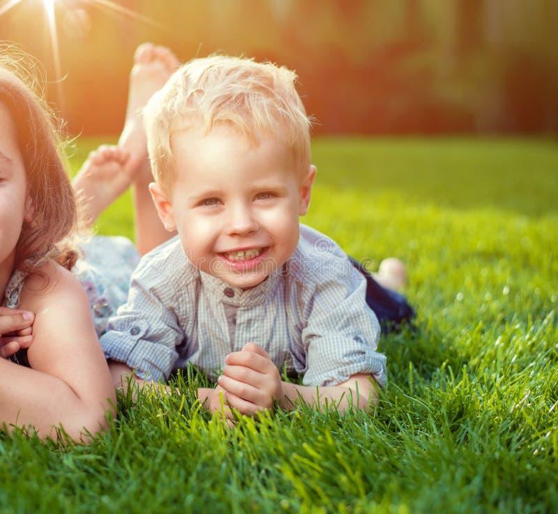 Nette Geschwister, die auf einem frischen Rasen sich entspannen stockfotos