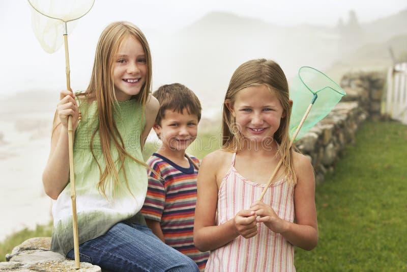 Nette Geschwister mit Fischernetzen am Yard stockfotografie