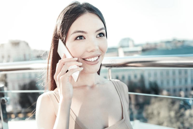 Nette gesprächige Frau, die Mobiltelefon nahe Kopf lächelt und hält lizenzfreie stockfotografie