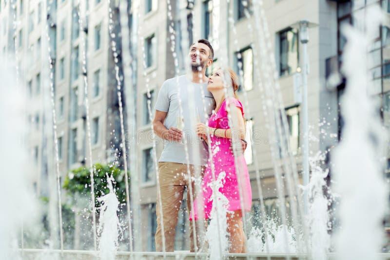Nette glückliche angenehme Paare, die den Brunnen bewundern lizenzfreies stockfoto
