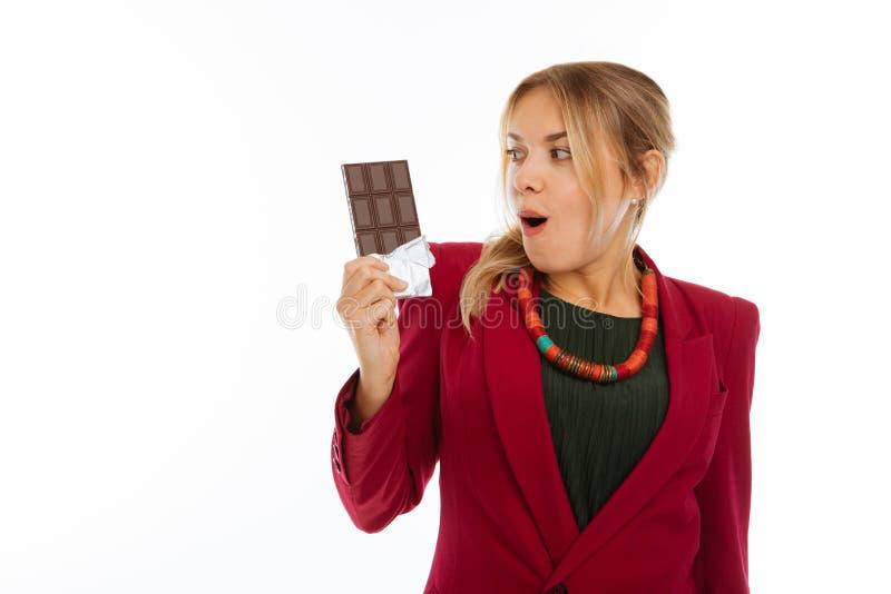 Nette glückliche aufgeregte Frau, die ihre Schokolade betrachtet stockbild