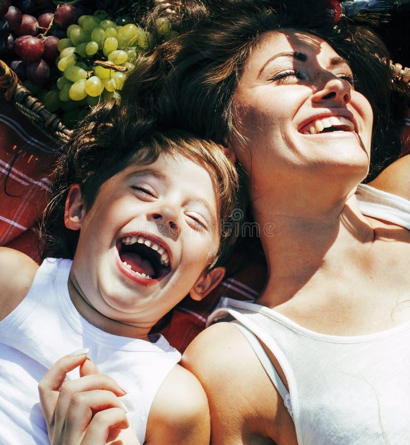 Nette glückliche Familie auf dem Picknick, das nah auf Mutter und Kinder des grünen Grases legen, den warmen Sommerferien oben, B lizenzfreie stockbilder
