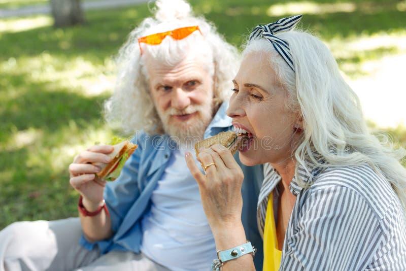 Nette glückliche Frau, die ein Sandwich isst stockfotografie