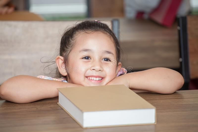 Nette glückliche kleine Studentin, die auf Tabelle mit Buch in der Volksschule des Klassenzimmers sich lehnt Kinder- oder Kinderk stockfoto