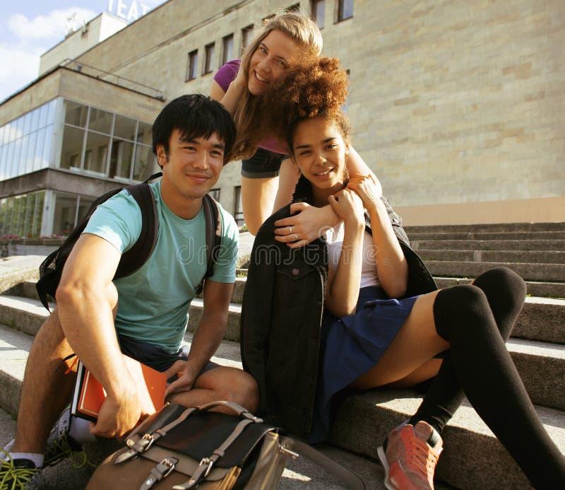 Nette Gruppe teenages am Gebäude der Universität mit Bücher huggings, zurück zu Schule stockbilder