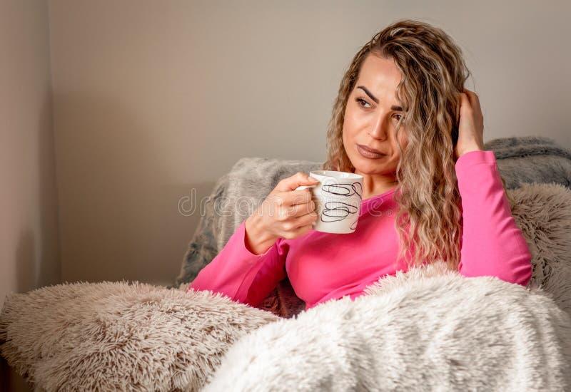 Nette hübsche Frau mit der Schale des heißen Getränks sitzend und auf Couch lächelnd stockfotos