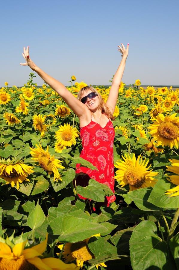 Nette hübsche Frau steht unter blühenden Sonnenblumen mit den angehobenen Händen bis zum klaren blauen Himmel lizenzfreie stockbilder