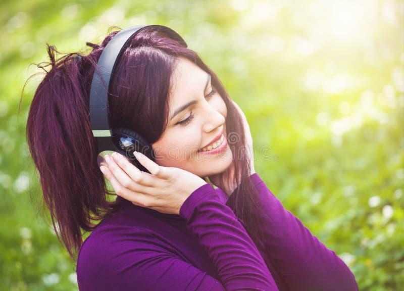 Nette h?rende Musik der jungen Frau mit Kopfh?rern lizenzfreie stockfotos