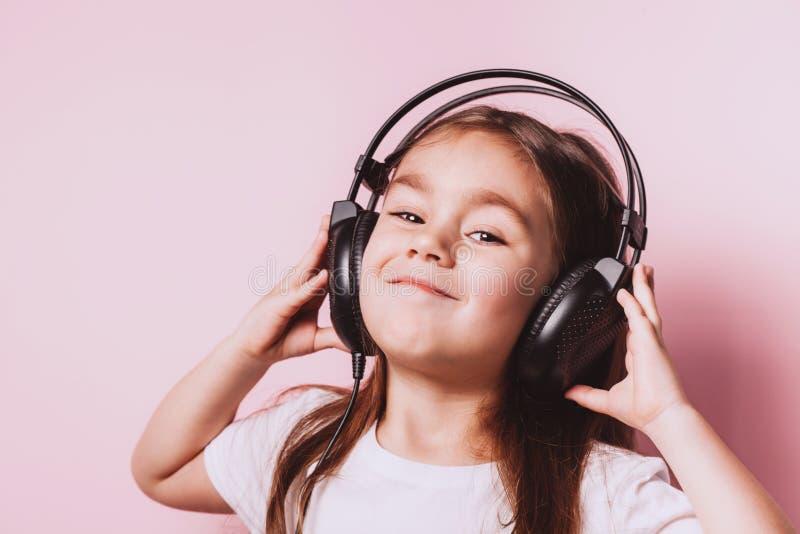 Nette h?rende tragende Kopfh?rer der Musik des kleinen M?dchens lizenzfreies stockfoto