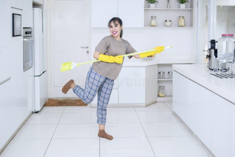 Nette Hausfrau, die Gitarre mit einem Besen spielt lizenzfreie stockfotos