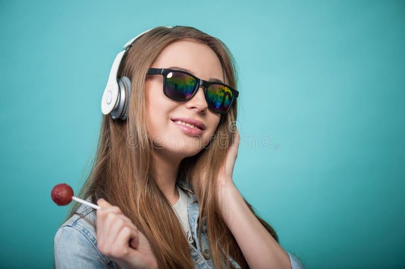 Nette Hippie-Frau mit Kopfhörern und Süßigkeit lizenzfreies stockfoto