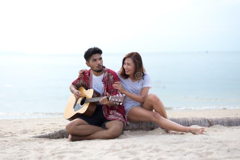 Nette hispanische Paare, welche die Gitarre ein Ständchen bringt auf Strand spielen stockbild