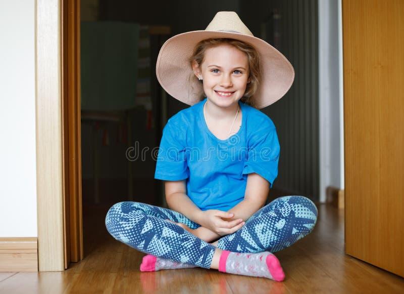 Nette 8 Jahre alte Mädchen, die auf dem Boden in ihrem Raum sitzen stockfotos