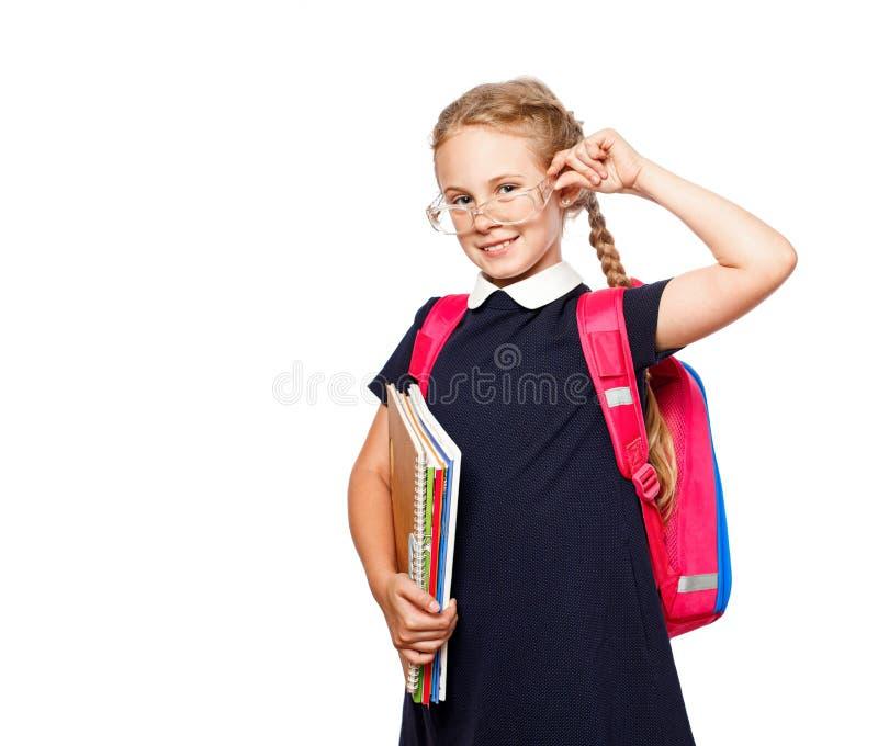 Nette 8 Jahre alte Schulmädchen mit dem Rucksack, der einheitliche Stellung lokalisiert über weißem Hintergrund trägt Bereiten Si stockfotografie