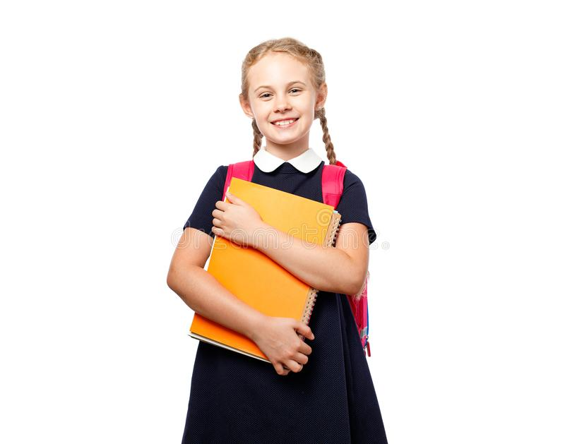 Nette 8 Jahre alte Schulmädchen mit dem Rucksack, der einheitliche Stellung lokalisiert über weißem Hintergrund trägt Bereiten Si stockbilder
