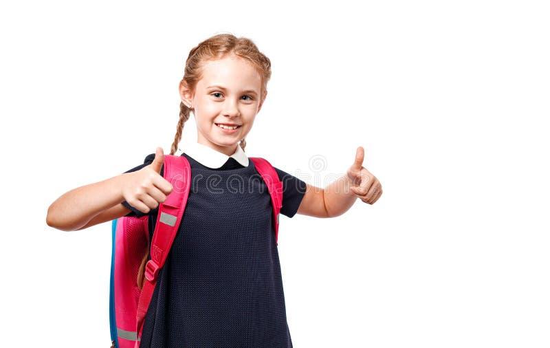 Nette 8 Jahre alte Schulmädchen mit dem Rucksack, der einheitliche Stellung lokalisiert über weißem Hintergrund trägt Bereiten Si stockfotos