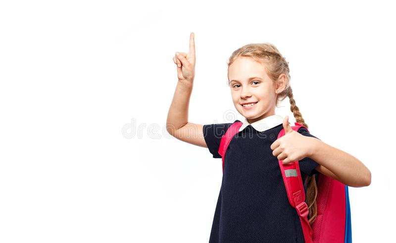Nette 8 Jahre alte Schulmädchen mit dem Rucksack, der einheitliche Stellung lokalisiert über weißem Hintergrund trägt Bereiten Si lizenzfreies stockbild