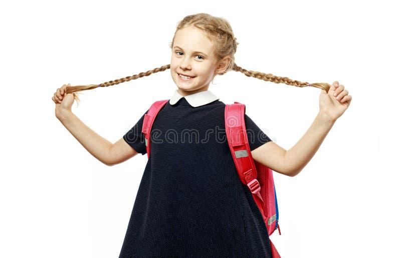 Nette 8 Jahre alte Schulmädchen mit dem Rucksack, der einheitliche Stellung lokalisiert über weißem Hintergrund trägt Bereiten Si lizenzfreie stockfotos