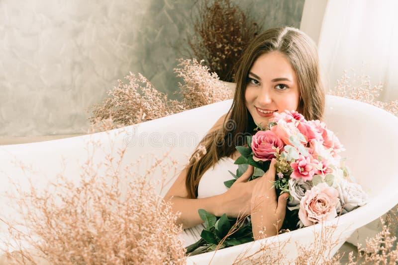 Nette jugendlich Frau, die in der Badewanne mit Blumenweinlesekunst lächelt stockfoto
