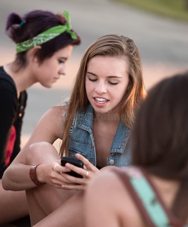 Nette jugendlich Mädchen, die Telefon verwenden stockbild