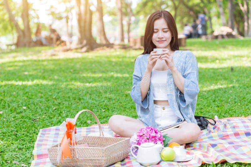 Nette jugendlich trinkende heiße Milch während Picknick, das auf Matte sitzt lizenzfreie stockfotografie