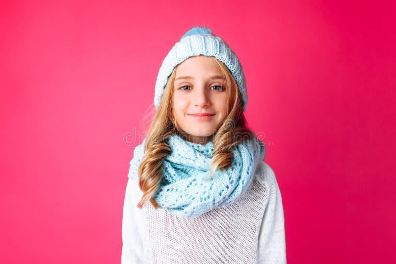 Nette Jugendliche in der weißen Strickjackenstellung lokalisiert auf rosa BAC stockbilder