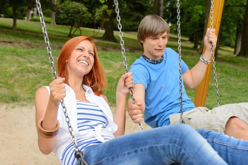 Nette Jugendpaare auf Schwingen im Park stockbild