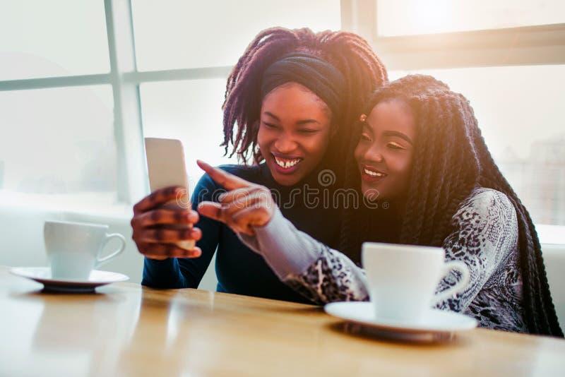 Nette junge afrikanische Frauen sitzen zusammen Sie lächeln und zeigen am weißen Telefon Modelle sitzen AR-bringht Fenster lizenzfreie stockfotografie