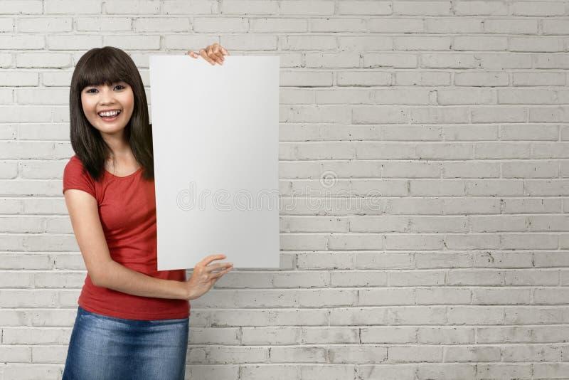 Nette junge asiatische Frau, die ein weißes leeres Papier hält lizenzfreie stockbilder