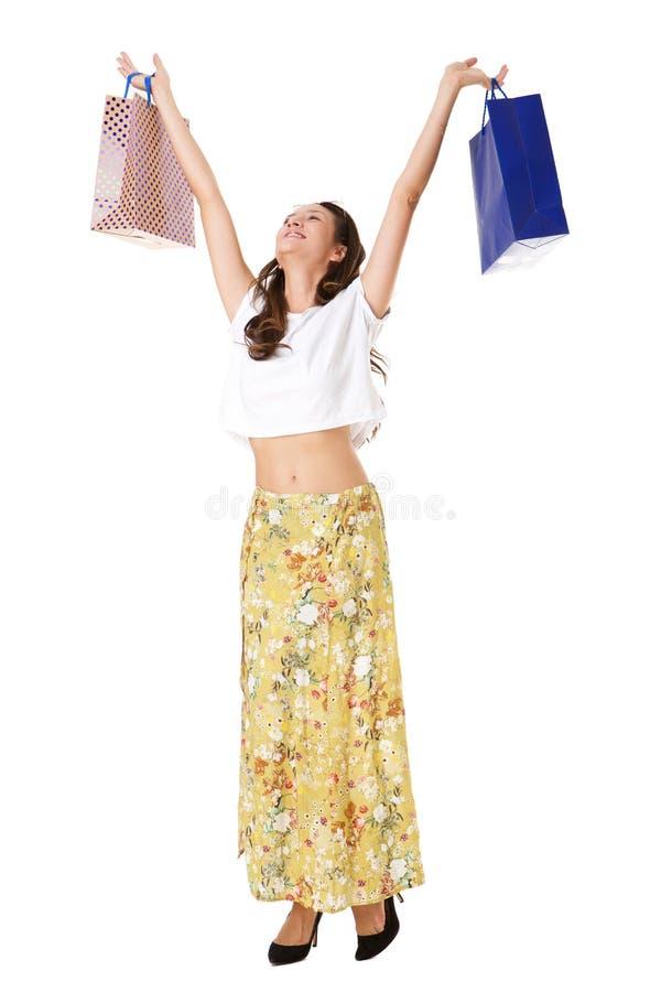 Nette junge asiatische Frau, die Einkaufstaschen oben gegen lokalisierten weißen Hintergrund hält stockfoto