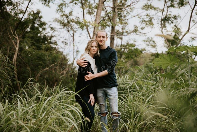Nette Junge-attraktive Datierung verbinden das Schauen, das Lächeln und das Lachen in dichten grünen tropischen Forest Jungle lizenzfreie stockfotos