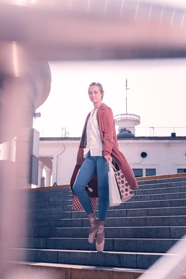 Nette junge Ballerina, die mit Einkaufstaschen steht lizenzfreie stockfotografie